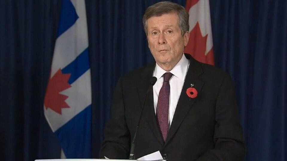 Il est en conférence de presse, devant les drapeaux de Toronto et du Canada.