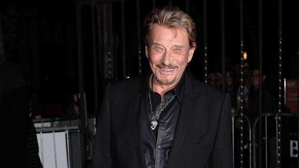 Le chanteur vêtu d'un complet noir sourit à la caméra.