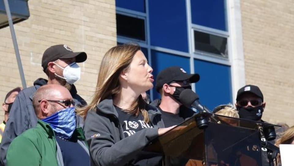 Charlene Johnson s'adresse à la foule en parlant dans un micro.