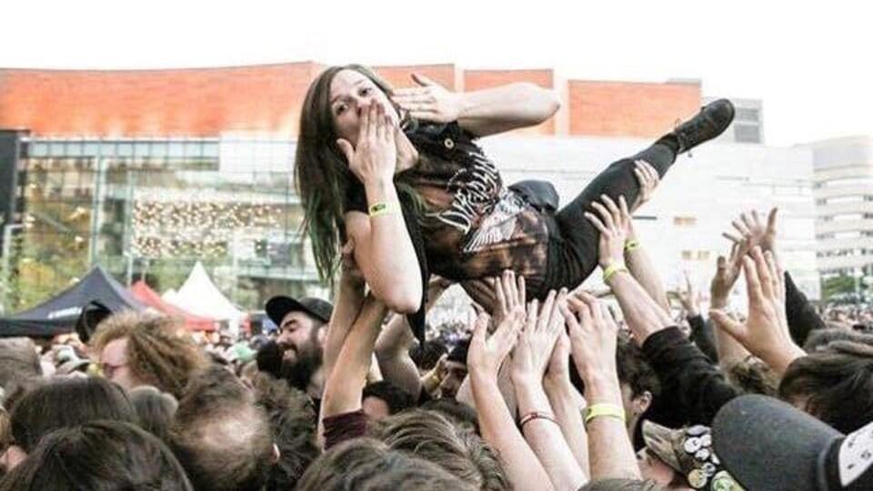Une femme est transportée par plusieurs personnes qui la tiennent au bout de leurs bras dans un concert extérieur.