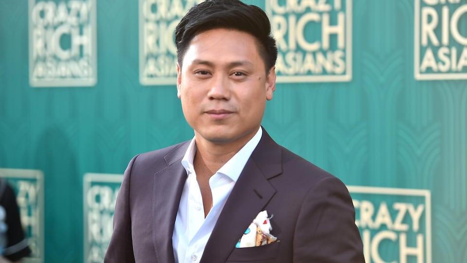 Le réalisateur Jon M. Chu regarde l'objectif de la caméra devant un grand panneau faisant la promotion du film «Crazy Rich Asians».