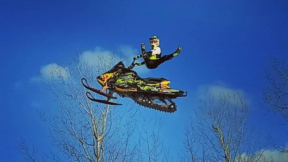 Un homme fait une acrobatie lors d'un saut à motoneige.