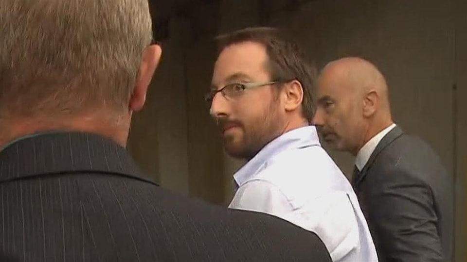 Jonathan Bettez escorté par deux policiers à son arrivée au palais de justice de Trois-Rivières en août 2016.