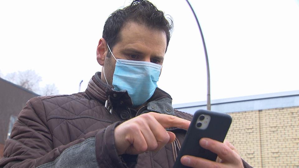 Un homme masqué manipule son téléphone intelligent.