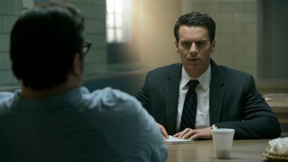 Le personnage de Holden Ford écoute un personnage qu'on voit de dos.
