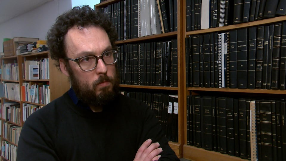 Jonathan Livernois en entrevue à Radio-Canada. Il porte des lunettes, a les bras croisés et se tient debout, à côté d'une bibliothèque murale.