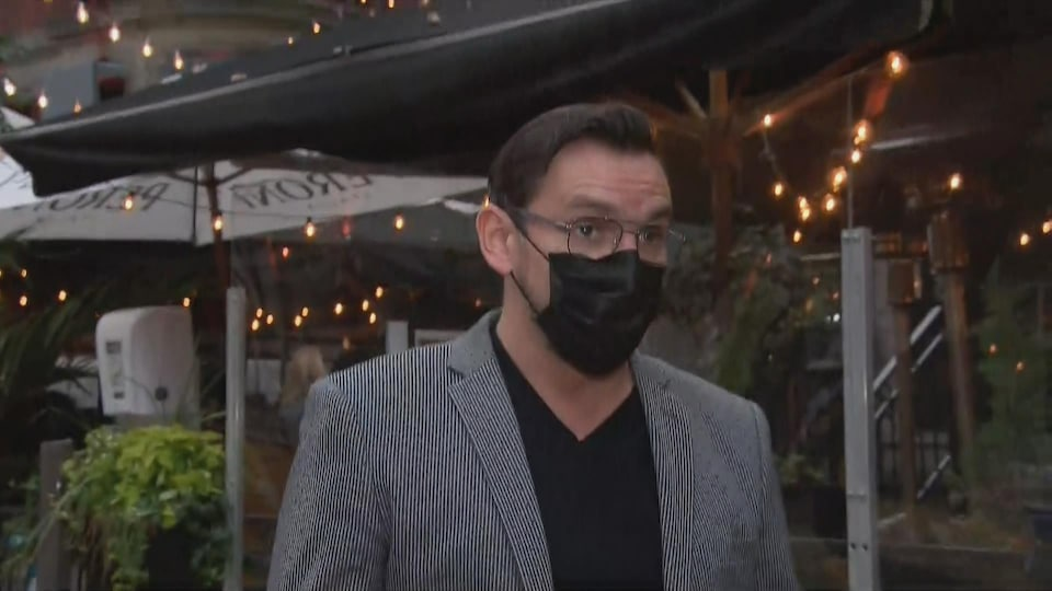Il porte un masque et regarde la journaliste.