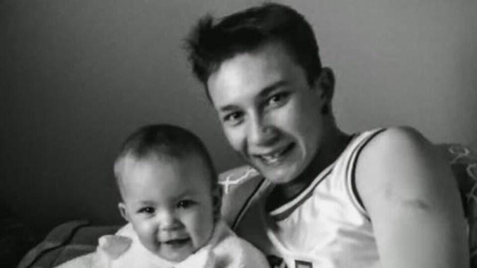 Le jeune autochtone, un bébé dans les bras, sourit à la caméra.