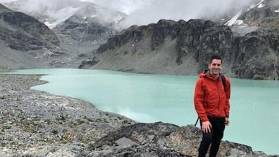 Jordan Naterer posant devant un lac dans les Rocheuses.