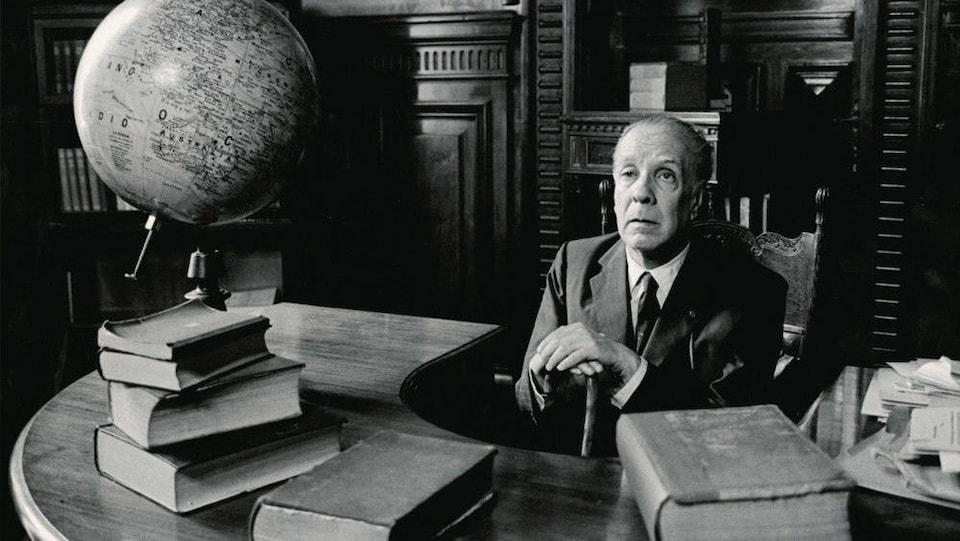 Portrait de Jorge Luis Borges assis sur un bureau en demi-cercle, dans une bibliothèque. 5 gros livres se trouvent sur le bureau.