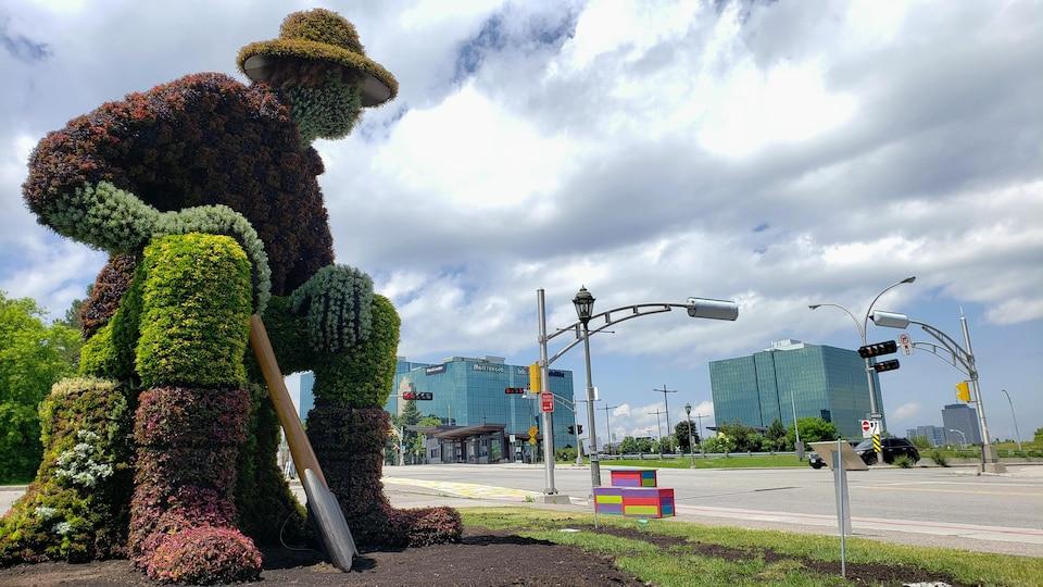 La sculpture de grande taille est recouverte de plantes et de fleurs.
