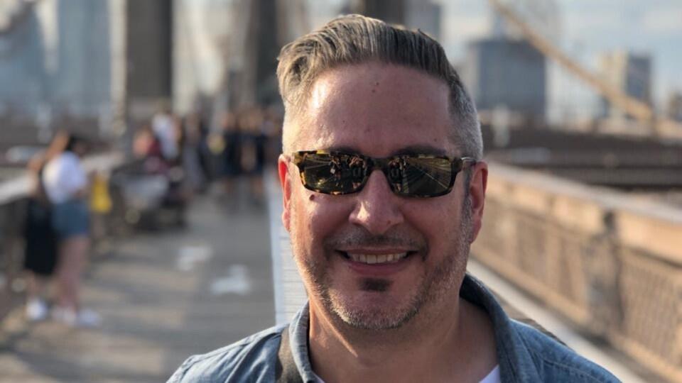 Un homme seul debout devant sur un pont et portant des lunettes.