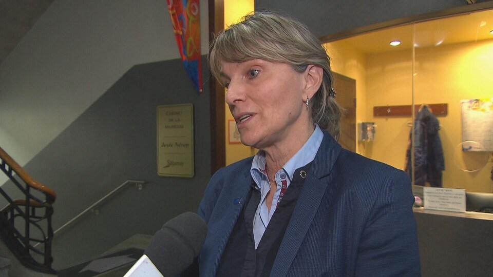 Une femme accorde une entrevue à Radio-Canada à l'hôtel de ville de Saguenay.