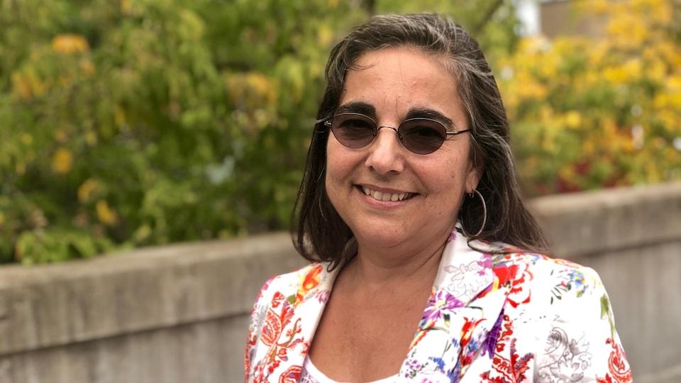 Une femme au veston fleuri porte des lunettes soleil.