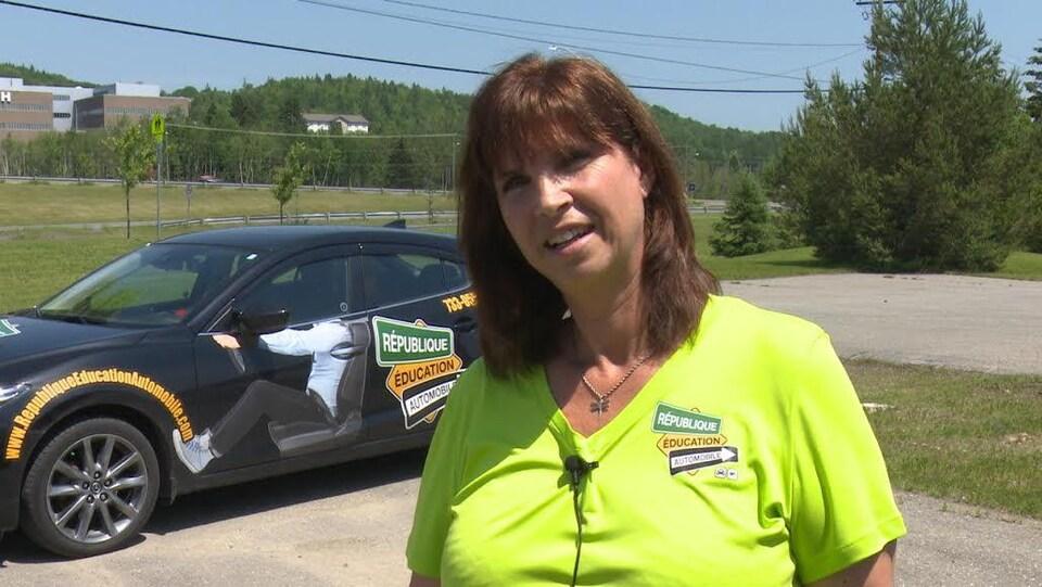Josée Racine en entrevue devant une voiture de son école de conduite.