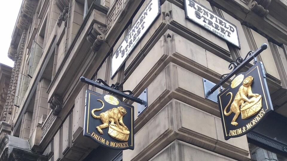 La photo montre le coin de rue où est situé le pub, avec son affiche qui montre un singe jouant du tambour.