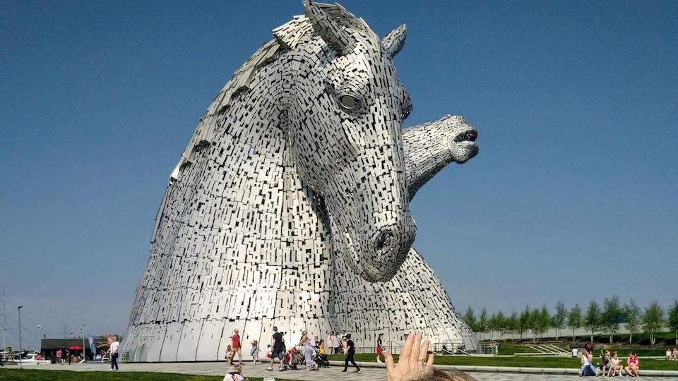 Une femme montre derrière elle des statues géantes représentant des têtes de chevaux.