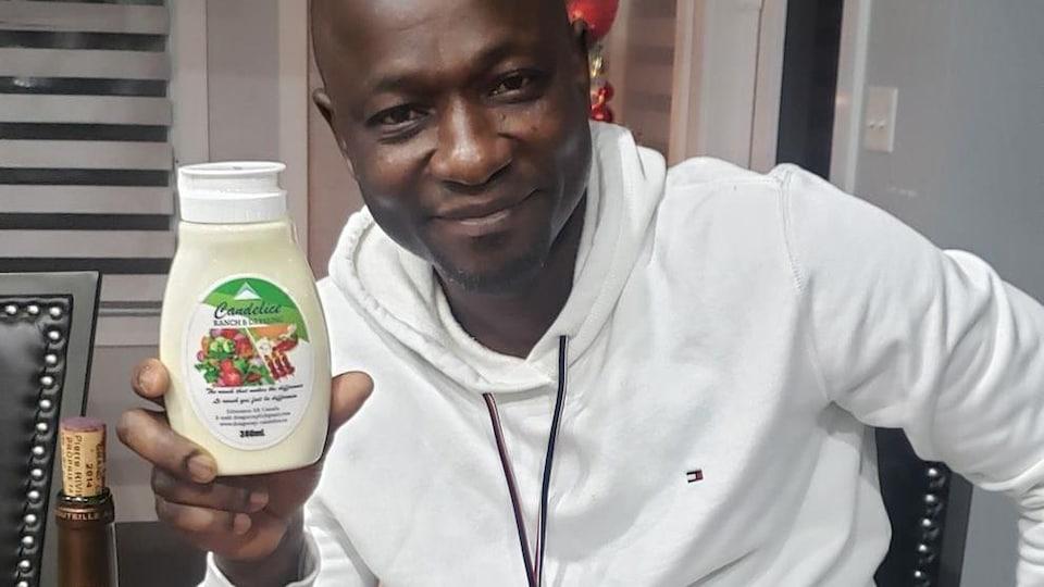 Joseph Dongo montre une bouteille de sa vinaigrette.