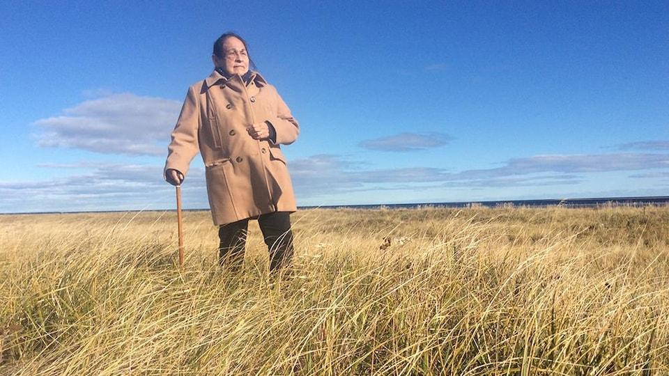 Joséphine Bacon se tient au milieu d'un terrain vague.