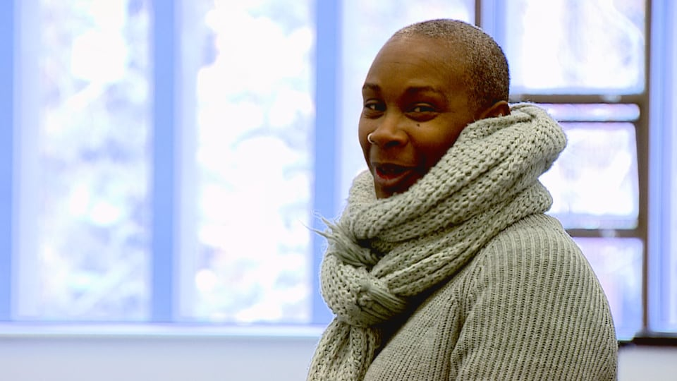 Une femme noire avec le crâne rasé et une grosse écharpe grise autour du cou.