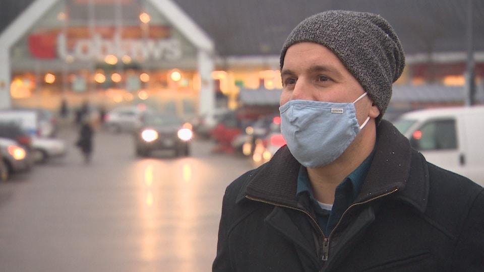 Un homme portant un masque et une tuque, devant un supermarché Loblaws.