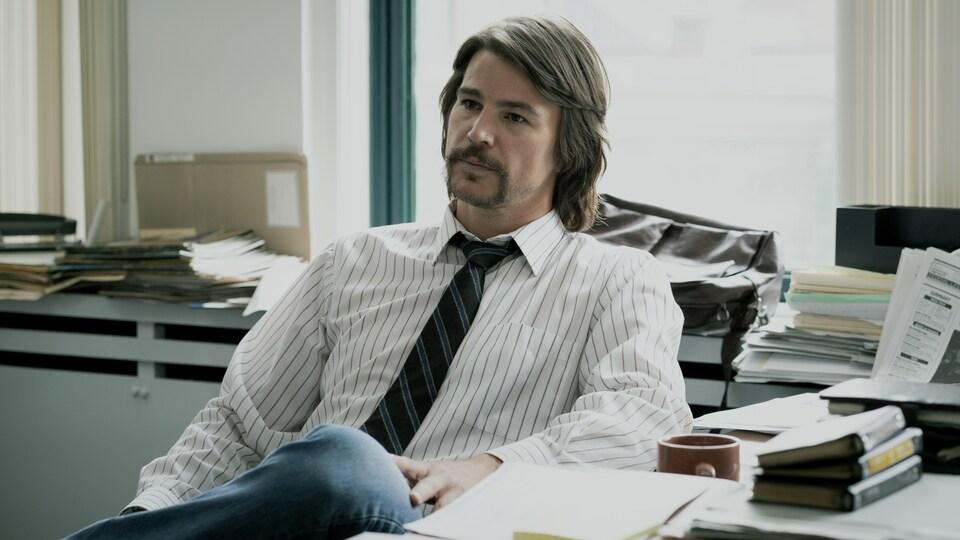 Un homme avec les cheveux mi-longs, vêtu d'une chemise lignée et d'une cravate bleue, est assis à son bureau.