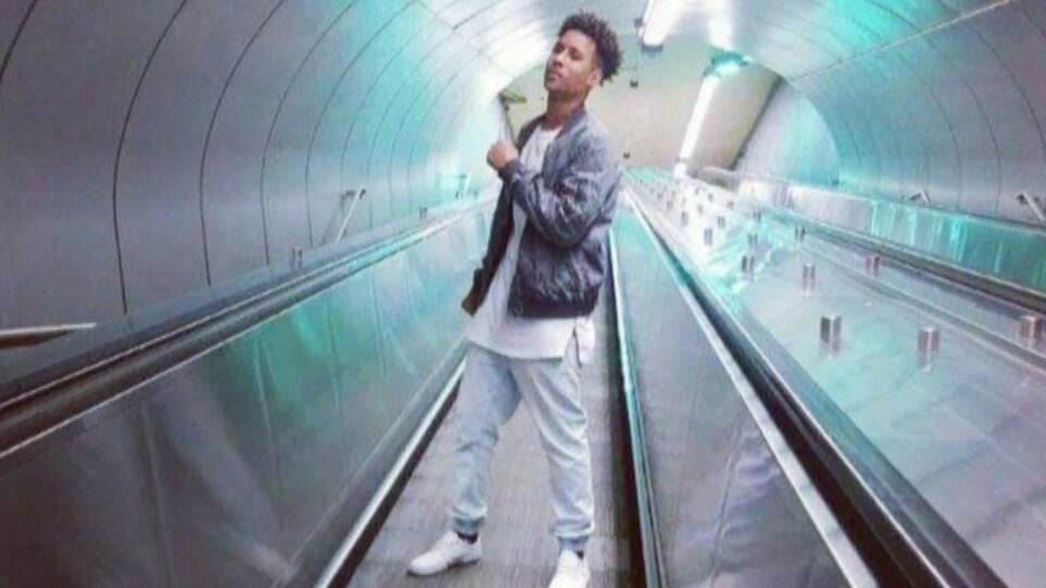 Un jeune homme pose sur un tapis roulant dans une station de métro.