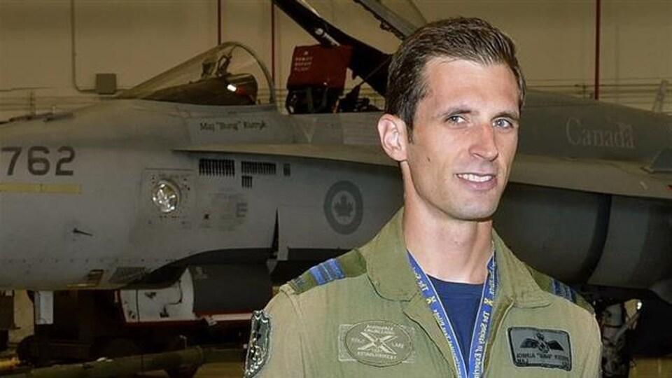 Un homme en tenue de pilote de chasse est devant un avion de chasse.