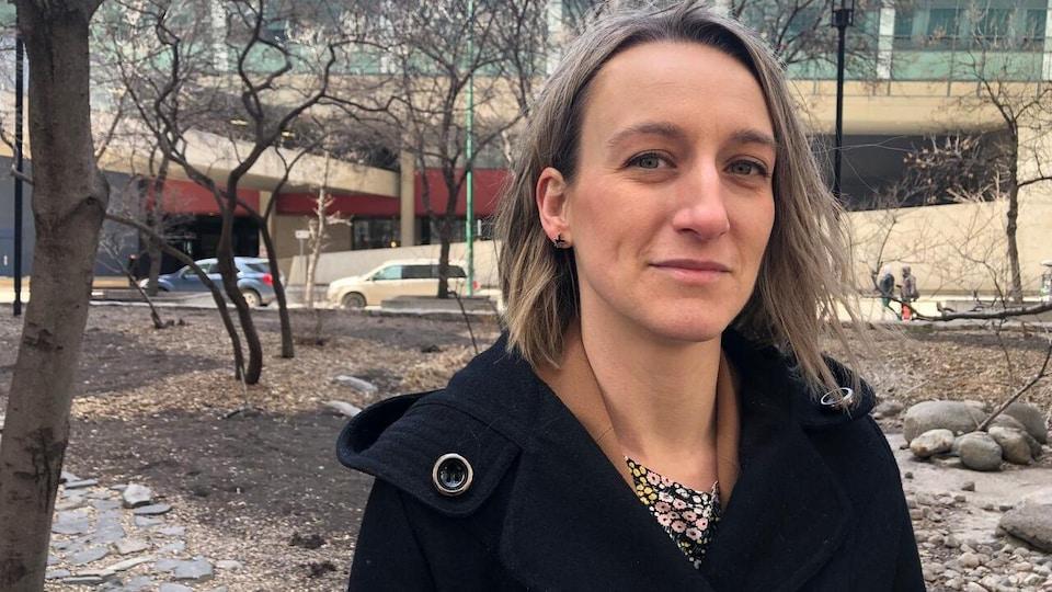 Joss Reimer est photographiée à l'extérieur du Cemtre des sciences de la santé. Elle regarde la caméra en souriant légèrement.