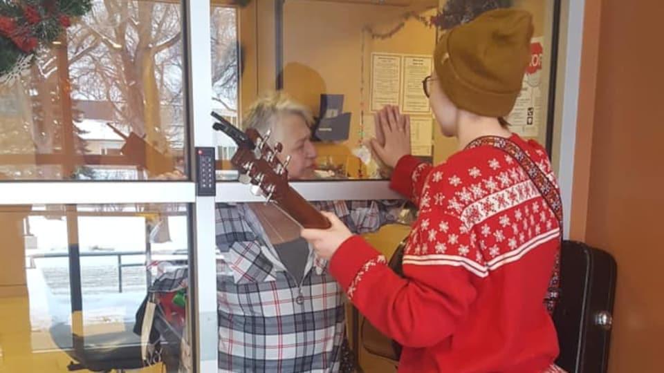 La guitare à la main et un chandail de Noël sur le dos, Janelle Campagne est avec sa grand-mère, mais une vitre les sépare.