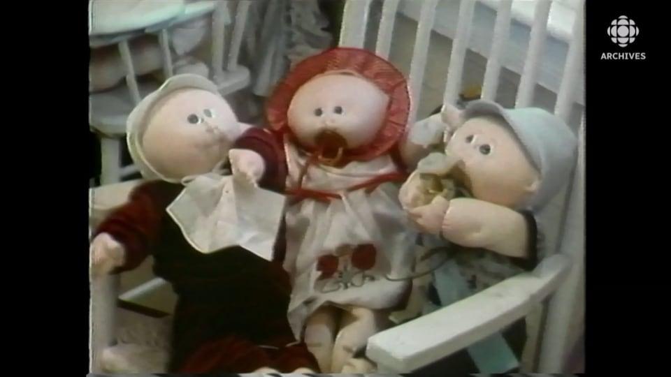 Trois poupées Bout d'chou sont assises sur une chaise berçante.