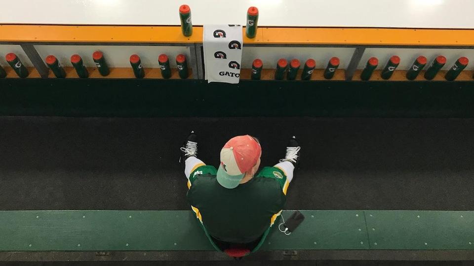 Un joueur de l'équipe de hockey junior des Broncos est assis seul sur son banc en écoutant de la musique et regarde la patinoire.