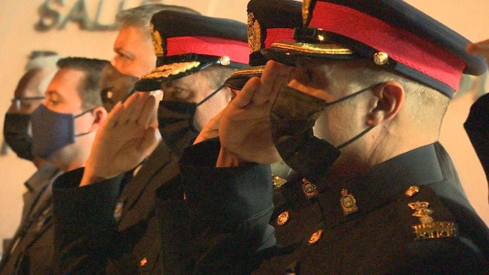 Des policiers font un salut.