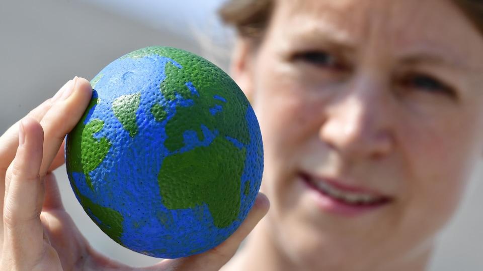 Une femme tient une boule représentant la planète dans sa main.