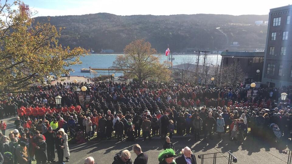 Plusieurs personnes sont réunies devant un monument en mémoire des soldats.
