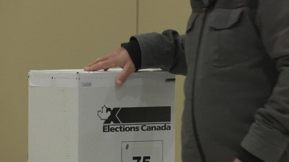 Une main sur une boîte de scrutin d'Élections Canada