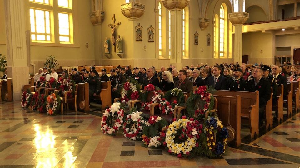 Des gerbes de fleurs sont déposées devant les bancs de l'église. Les gens sont assis derrière.