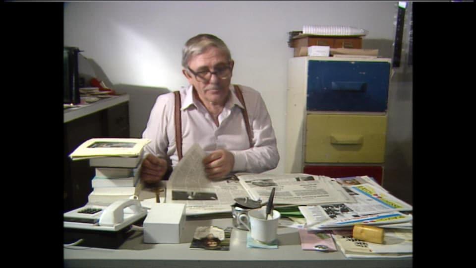 Un homme dans la soixantaine assis à un bureau consulte un journal.