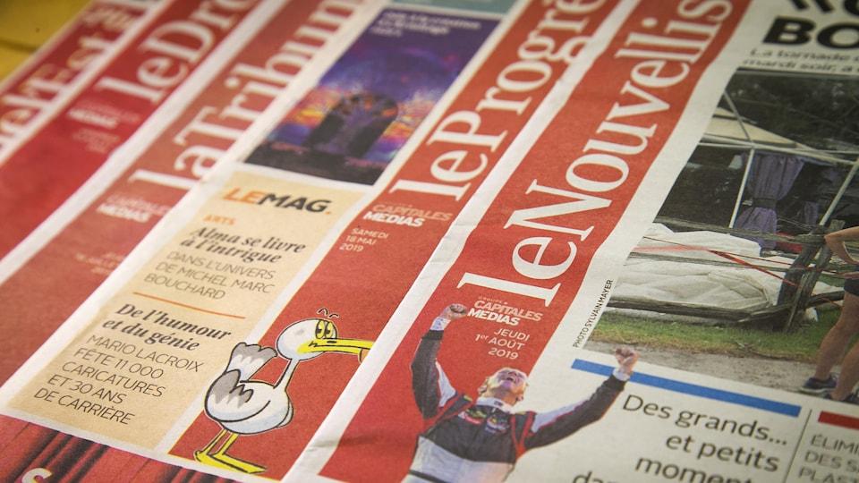 Des journaux de Groupe Capitales Médias empilés de manière à ce qu'on en voie le titre.