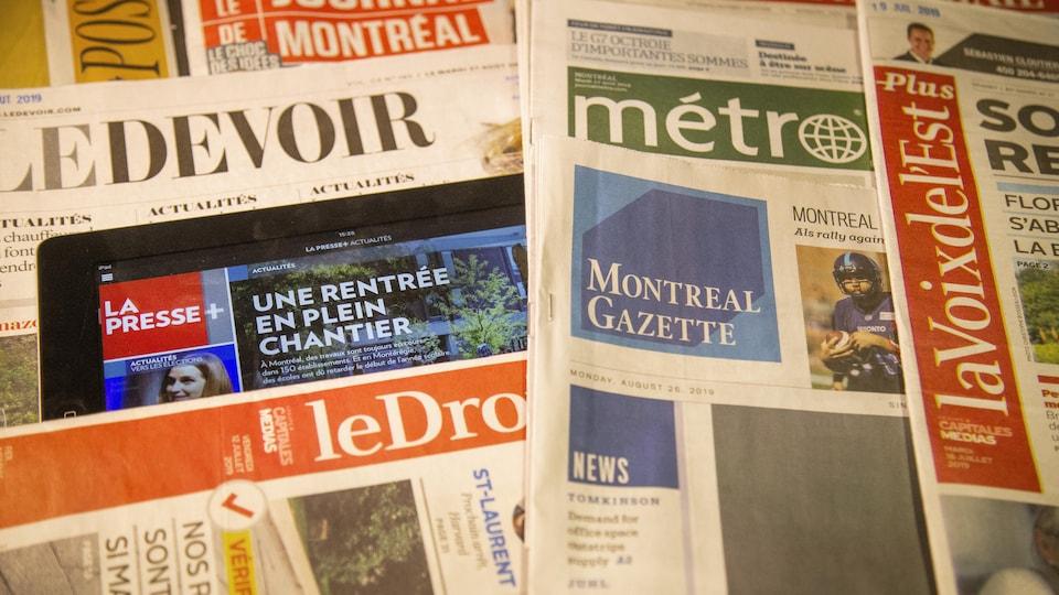 Des copies du Devoir, du Journal de Montréal, du journal Métro, de la Voix de l'Est, du Droit et un iPad montrant la Presse +