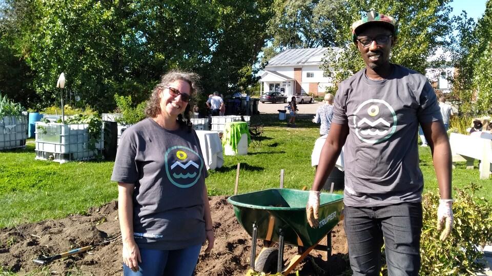 Deux personnes portant un t-shirt sur lequel est imprimé le logo de la MRC de Témiscamingue sourient dans un jardin.