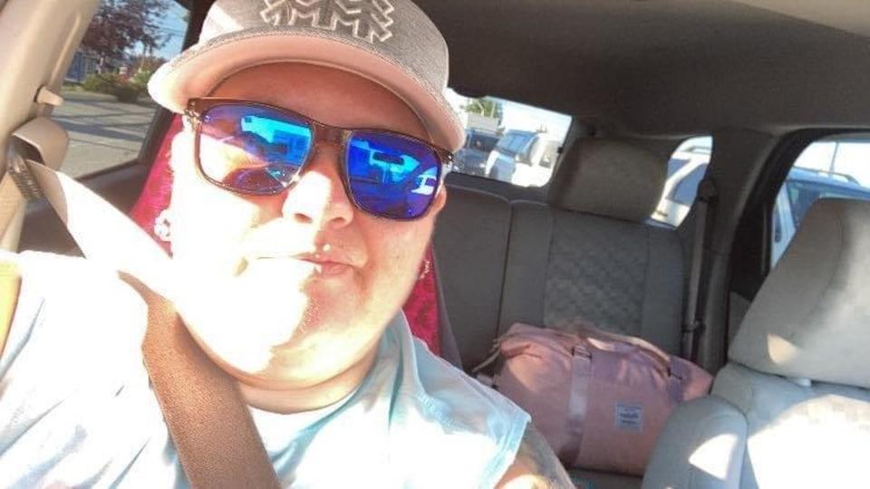Elizabeth Johnson dans sa voiture, porte une casquette et des lunettes de soleil.