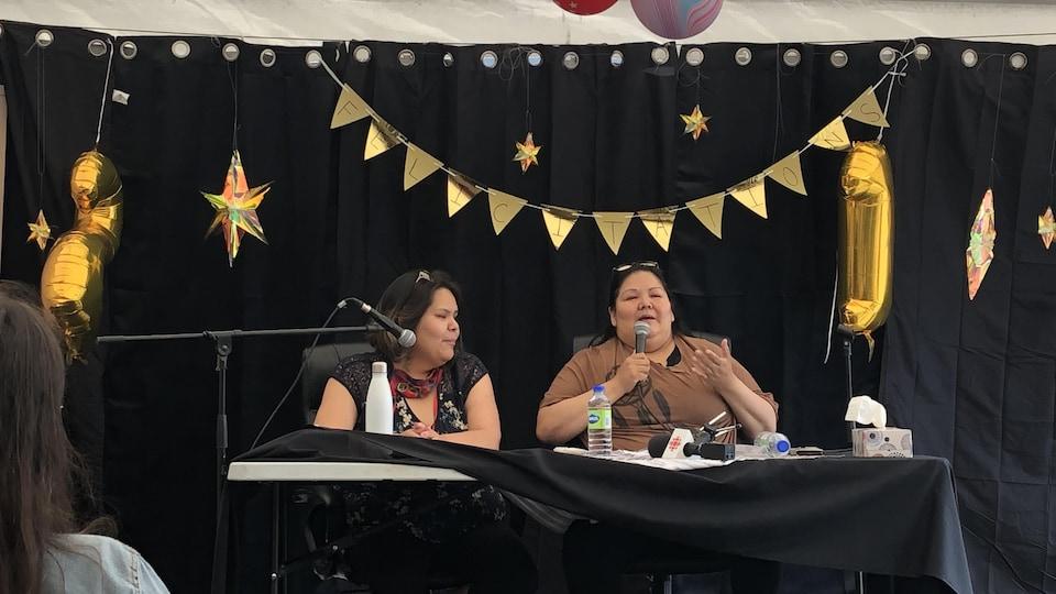 Joyce Grégoire et Nicole Wapistan sont installées à une table décorée de façon festive.