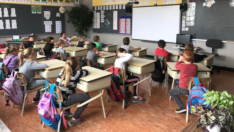 Des élèves regardent vers le tableau dans une classe du primaire.