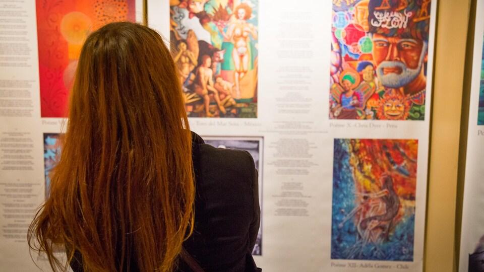 Une femme observe des oeuvres d'art.