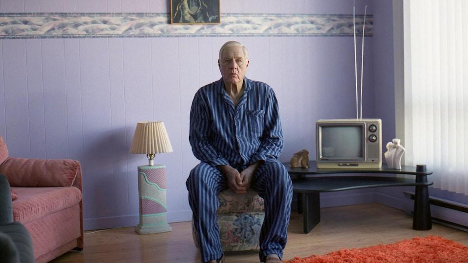 L'homme est assis dans un salon. La décoration n'est pas récente.