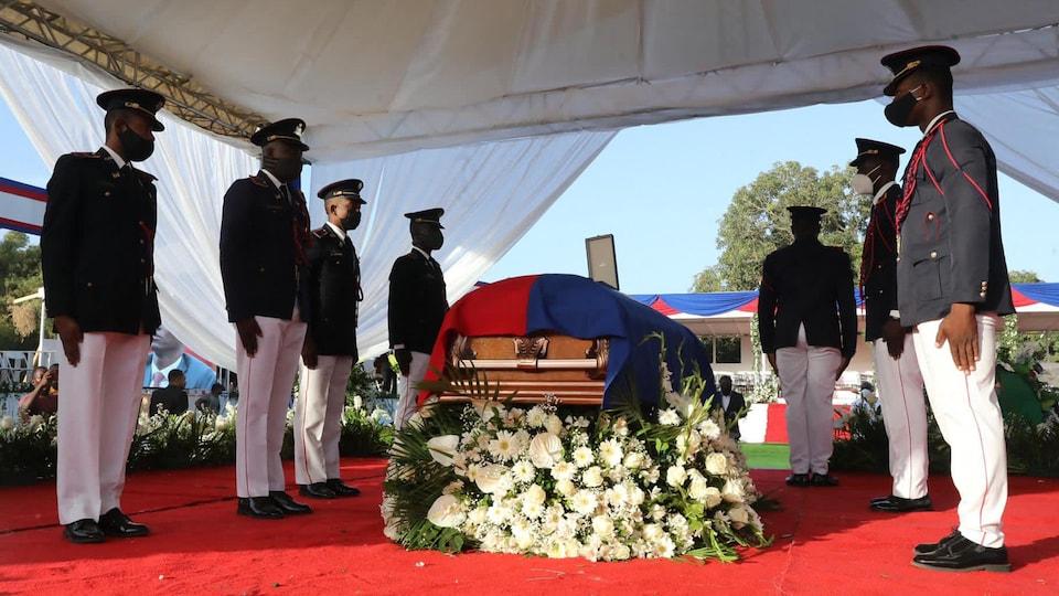 Des membres de la garde, en uniforme d'apparat, se tiennent devant un cercueil recouvert du drapeau haïtien.