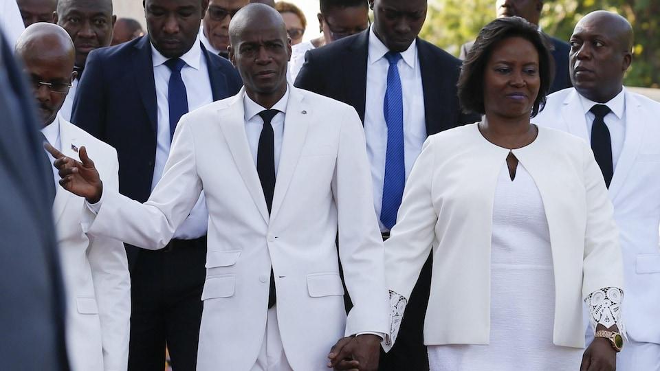 Jovenel Moïse et sa femme se tiennent par la main.