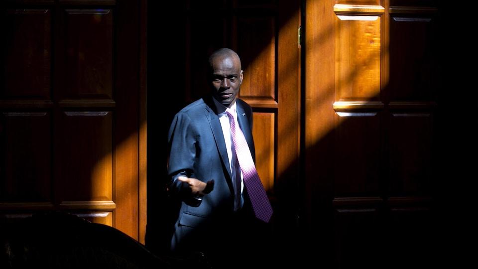 Jovenel Moïse photographié devant une porte dans un rayon de lumière.