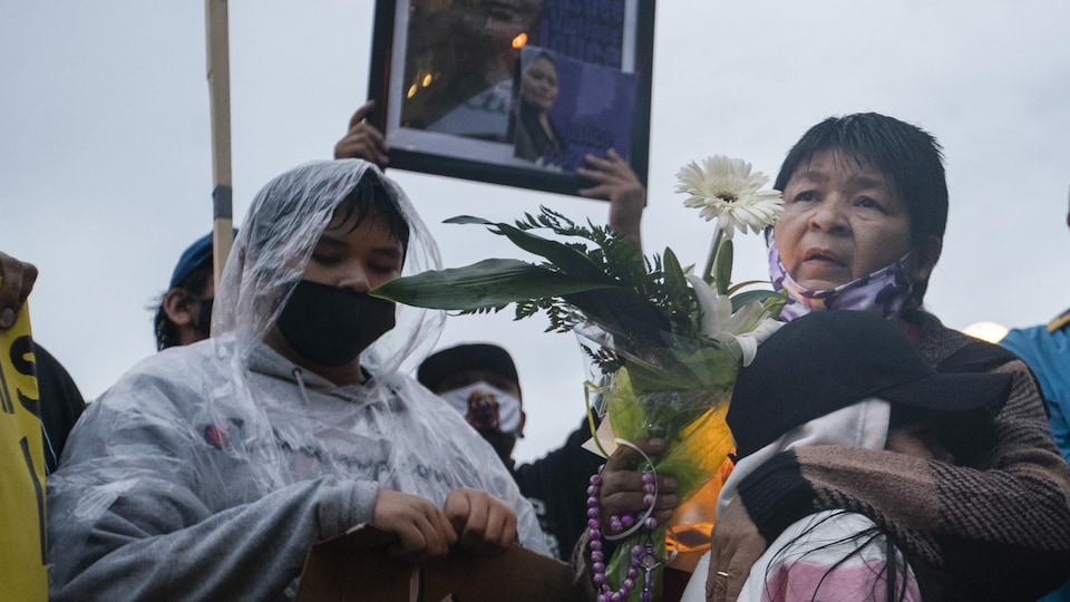 Des femmes parmi une foule tiennent des fleurs et des chandelles.